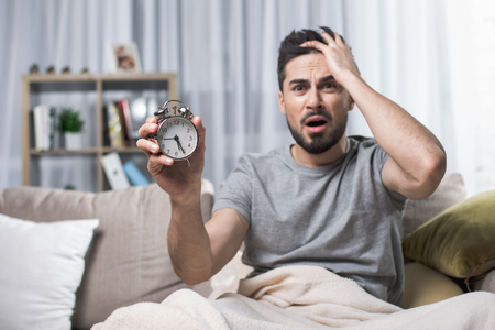 Waist up portrait of shocked handsome man sitting on couch. Focus on clock he is showing to camera in astonishment Reklamní fotografie - 97245876