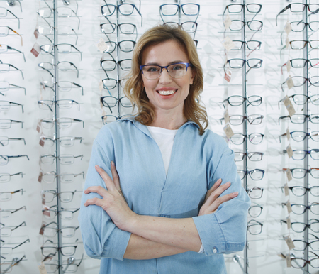 Portrait of beaming female client standing in glasses shop. Ophthalmology concept Stock Photo