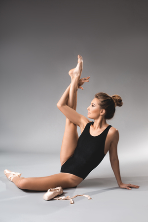 Ballerina in leotard sitting on the floor and demonstrating stretching of legs with smiling face Banco de Imagens