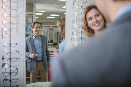 Portrait of happy young husband in modern glasses talking with glad wife in shop. Happy couple in optics shop concept Stock Photo - 97246303