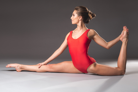 Profile of thin female person wearing red leotard doing the splits