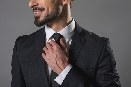 Cheerful successful happy young man in fashion business suit straightening tie. Isolated on gray background