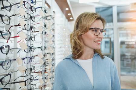 Side view happy young woman in glasses situating in optical store. Optics concept Stock Photo