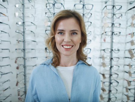 Portrait of cheerful woman choosing eyeglasses while looking at camera. Optics concept