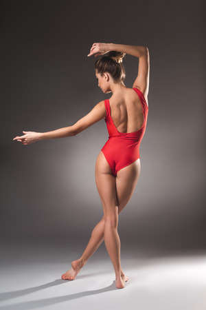 Young gymnast in leotard standing with her back with hands floating in air