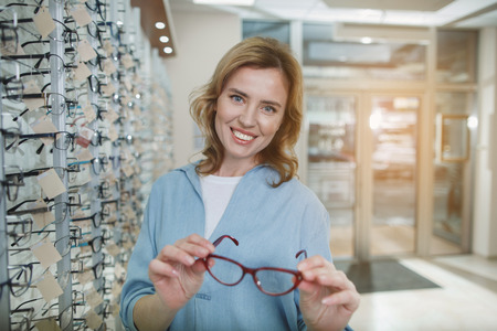 Portrait of beaming client watching at spectacle while locating in shop. Customer care concept Stock Photo - 97246377