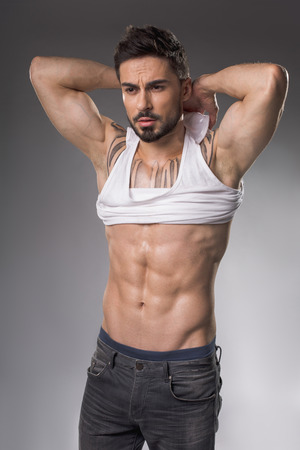 Portrait of solemn sexy macho with muscular body disrobing his torso. Isolated on background Banco de Imagens - 97246512