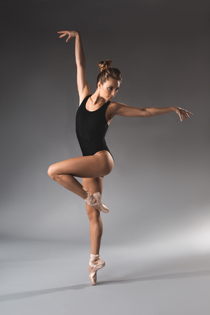 Longitud total de gimnasta femenina delgada en tricot negro que se balancea en la punta de los dedos de una pierna y manos que se elevan Foto de archivo - 97246517