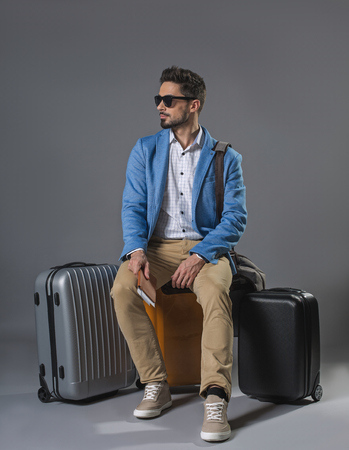 Full length portrait of handsome calm businessman in sunglasses with luggage. He is holding tickets in hand Archivio Fotografico - 97246521