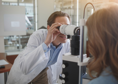 Outgoing ophthalmologist looking at special appliance. He checking eyes of female. Treatment concept Stock Photo