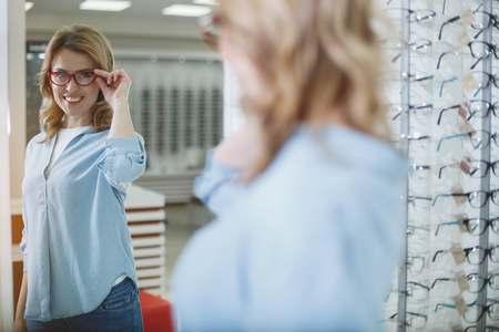 Portrait of beaming female client looking at mirror in optician store. Eyesight correction concept Stock Photo