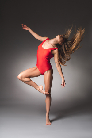 Full length of slim woman dancing in tight red swimsuit. Her hair are disbanded Banco de Imagens