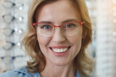 Portrait of woman wearing spectacles while expressing happiness in optician shop. Ophthalmology concept Stock Photo