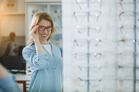 Outgoing lady admiring reflection in optician shop while holding eyeglasses by arm. Optics concept