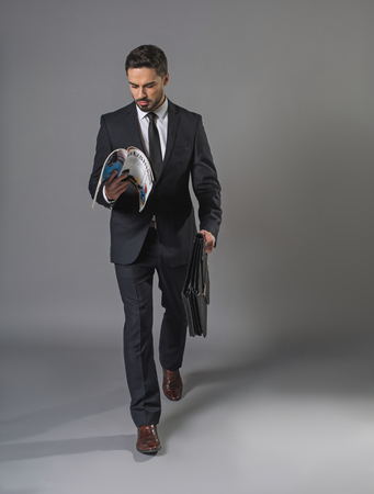 Full length of busy undistracted man in business suit. He is going with briefcase and reading a business periodical Stock Photo