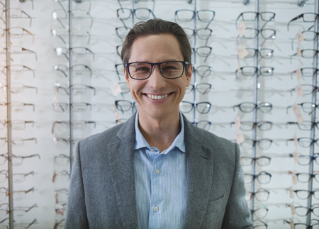 Portrait of beaming man in spectacles looking at camera while standing in optician shop. Visitor buying spectacles concept