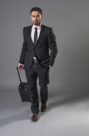 Full length portrait of young assured man going on business trip with luggage. He walking and keeping hand in pocket Stock Photo