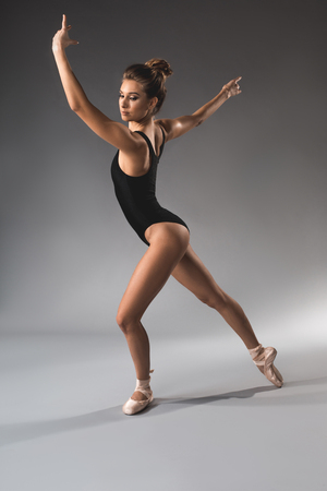 Full length of lightweight woman making ballet posing with confidence. She is wearing swimsuit