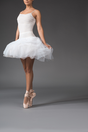 Gracefulness concept. Slim woman in tutu rising at the tips of her fingers. Copy space in right side