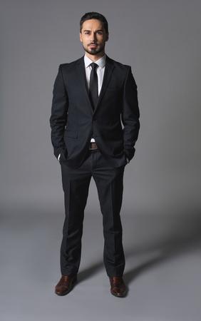 スーツとポーズで高貴なコンセントの男の完全な長さの肖像画。リーダーシップとブームの概念。彼は自信を持ってカメラを見ている 写真素材