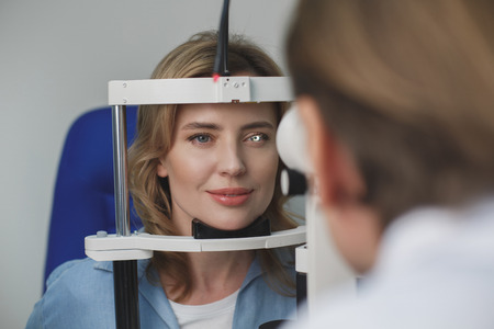Portrait of smiling female client checking eyesight with equipment opposite doctor. Ophthalmology concept