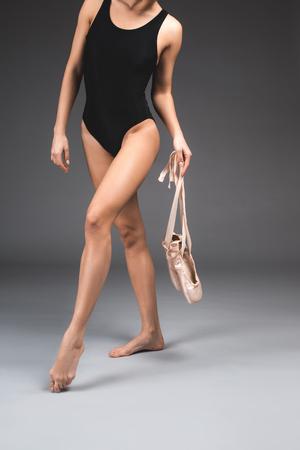 Ballerina posing with satin pointe in hands. Tight leotard emphasizing her slender figure