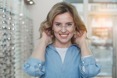 Portrait of cheerful woman in spectacles looking at camera. Optics concept