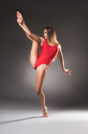 Serious young lady with athletic figure and loosen hair trying balancing on one leg