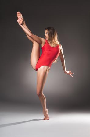 Ernstige jonge dame met atletische figuur en losse haren proberen balancerend op één been Stockfoto