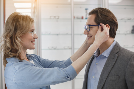 Side view beaming female wearing eyeglasses on male. They looking at each other. Glad couple in optician store concept 免版税图像