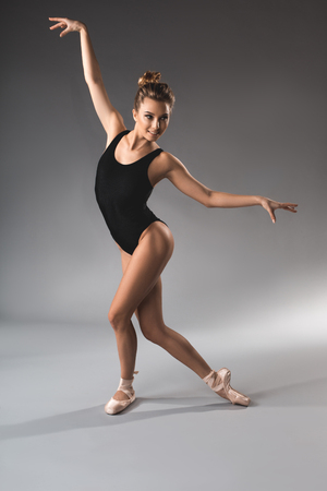 Sportive hobby concept. Full length portrait of glad ballet performer in tights and pointe making graceful movement