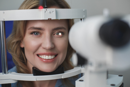 Portrait of close up cheerful female face examining eyesight with equipment. She looking at camera. Ophthalmology concept