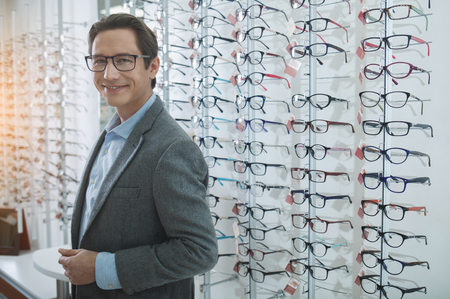 Portrait of smiling male situating in optician store. Client choosing eyeglasses concept