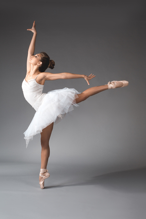 Ballet art concept. Full length of young woman wearing short dance skirt standing on tiptoes of one foot with gracefulness
