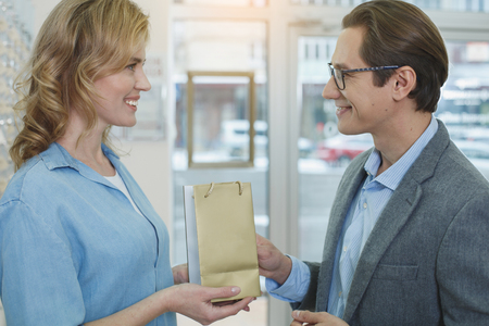 Side view smiling female giving package to beaming man. They standing in optician shop. Ophthalmology concept Stock Photo