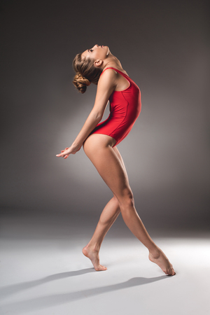 Side view of slender female gymnast in red swimsuit incurving her body backward Stockfoto
