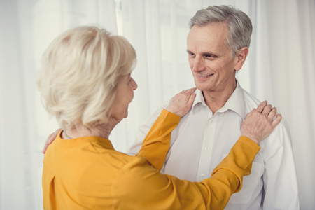 Caring female pensioner looking at her smiling elderly husband, her hands lying on his shoulders. White curtain on background Stock Photo