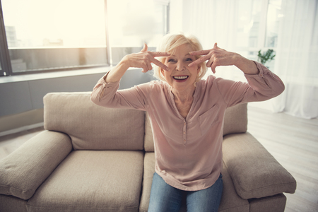Young soul. Portrait of happy senior woman fooling around while relaxing on cozy divan Stock Photo