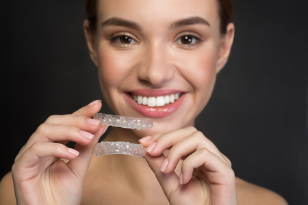 Ready to adjust my teeth. Optimistic young woman is holding transparent orthodontic device for improving bite. She is looking at camera with joy. Selective focus and isolated background