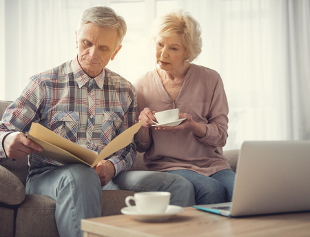Calm mature man and woman sitting in living room and looking at folder with papers Фото со стока