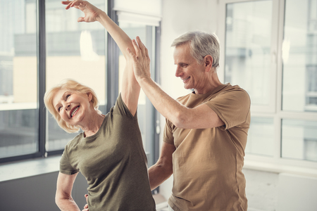 Cheerful grey haired woman standing with raised arm and smiling, old man beside her is helping with exercise