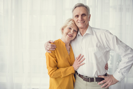 Waist up portrait of elderly wife and husband embracing each other and smiling. Copy space in left side Stock Photo