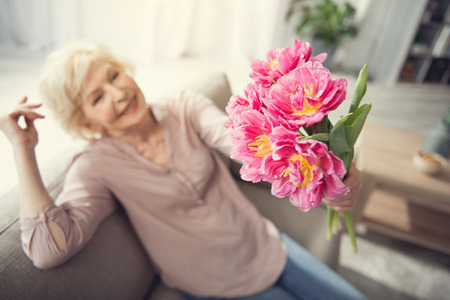 Senior woman sitting at home and looking at tulips in hands. Focus on flowers. Top view