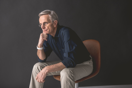 Side view pensive mature male keeping chin by hand while sitting on chair. Thoughtful employer concept