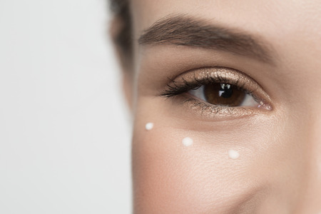 Facial cosmetics concept. Close up of smiley eye of girl. She is looking at camera with joy. Drops of moisturizer cream are around