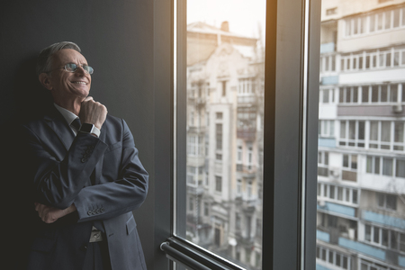 Portrait of pensive senior employer looking at window while leaning against wall indoor. He keeping chin by hand. Dreaminess during work concept Reklamní fotografie
