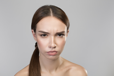 Feeling anger. Portrait of young disappointed naked woman is looking at camera with annoyance. Isolated background Reklamní fotografie