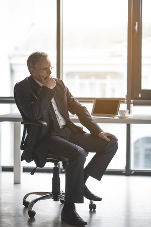 Full length side view pensive old businessman having job with digital device at table. Wistful employer in office concept Reklamní fotografie