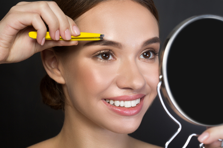 Close up portrait of gorgeous young woman is standing and using tweezers while looking at the mirror. She is plucking eyebrows with smile. Isolated background