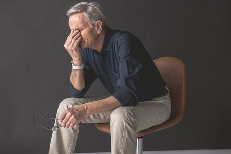Weary senior male sitting on chair while holding eyes by arm. Exhaustion during labor concept